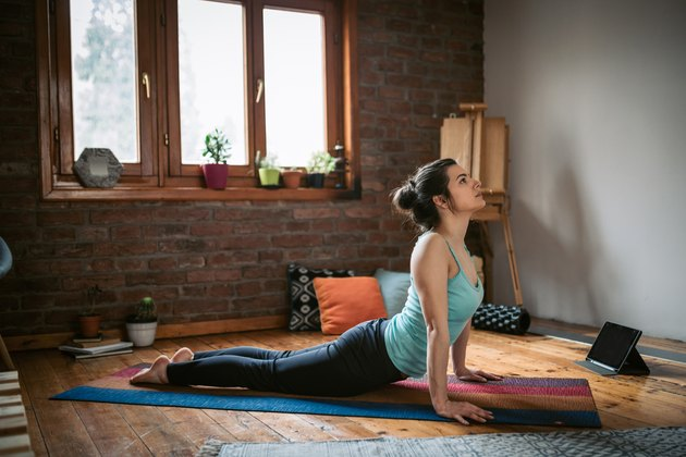 Woman stretching core muscles with Upward Facing Dog yoga pose