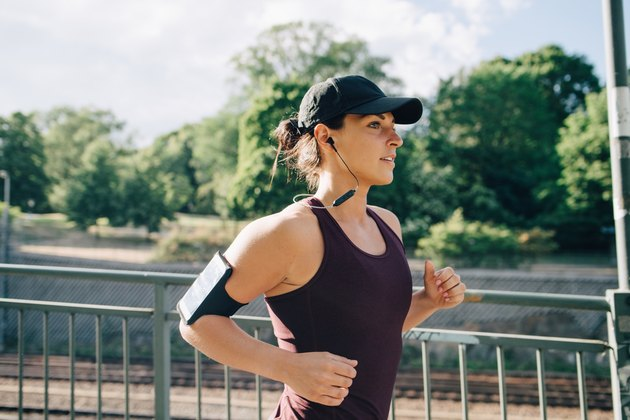 Confident sportswoman listening music while jogging on bridge in city