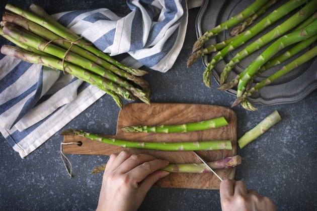 Fresh raw asparagus on stone background. Female hands cut asparagus on wooden cooking board. Top view