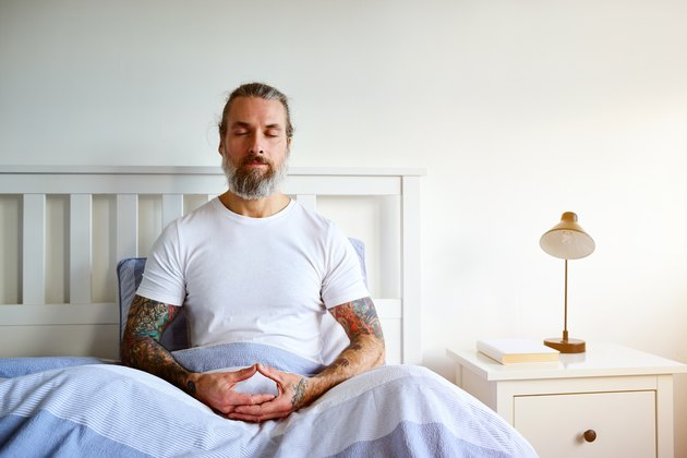 A mature man sitting in bed doing a 5 minute morning mediation to set his intentions for the day