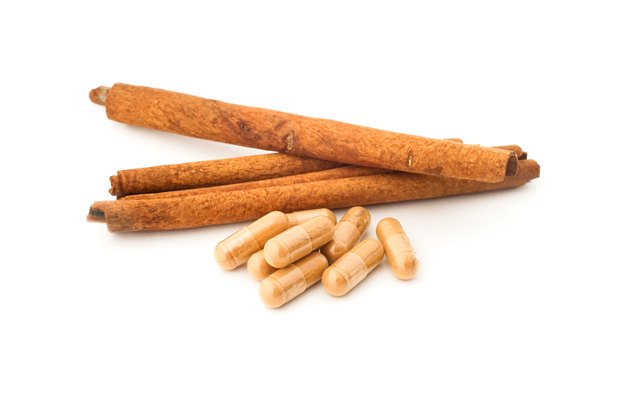 Cinnamon powder in pills with cinnamon sticks on white background