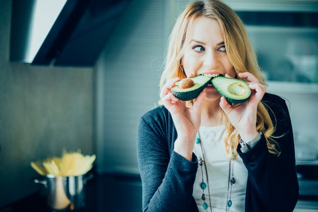 A woman biting into two avocados