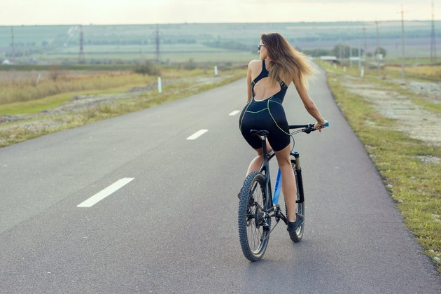 Girl on a mountain bike on offroad, beautiful portrait of a cyclist at sunset, Fitness girl rides a modern carbon fiber mountain bike.