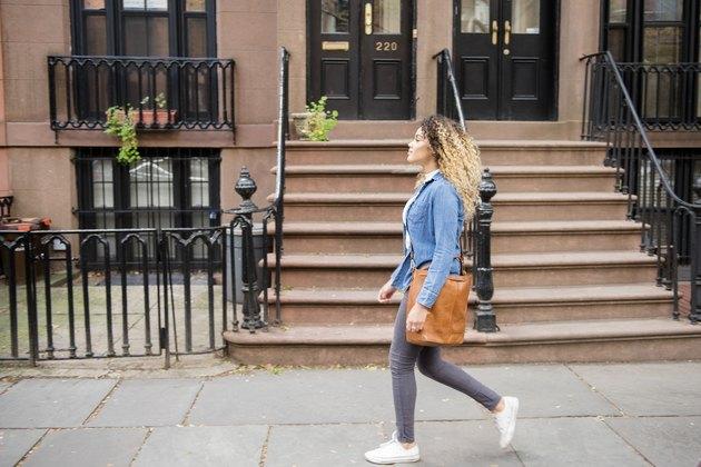 Mixed Race woman walking on city sidewalk