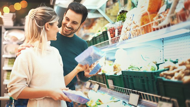 Couple shopping in supermarket for a cheap meal plan
