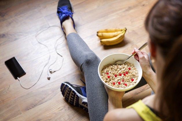 Fille mangeant une farine d'avoine avec des baies après une séance d'entraînement. Concept de remise en forme et de mode de vie sain.