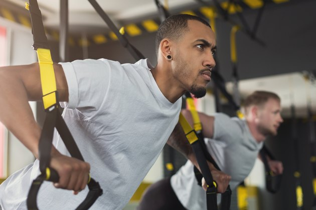 Men performing TRX exercises for upper body at the gym