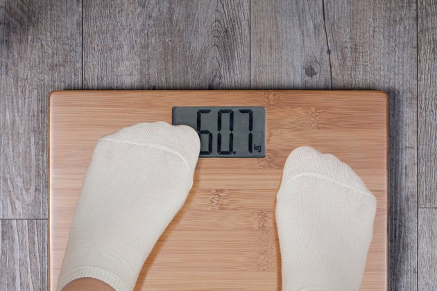 Legs of woman standing on weight scale and his thumb covering display.