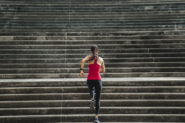 Fitness woman is running up the stairs.
