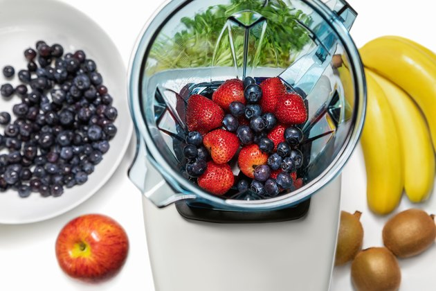 Strawberry and blueberries in blender with ingridients for smoot