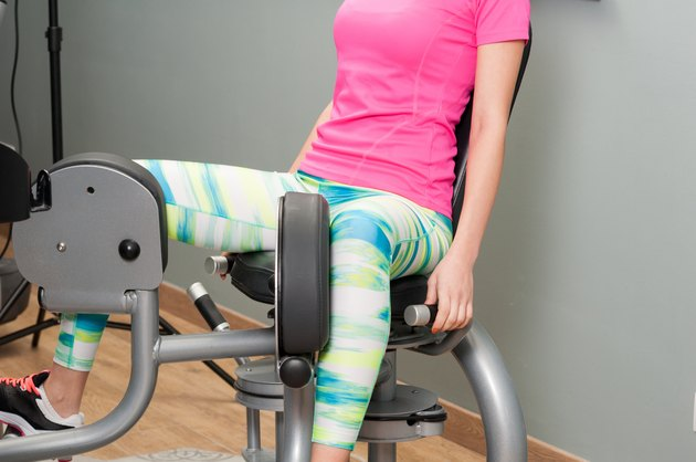 Young female training her thighs on stationary machine