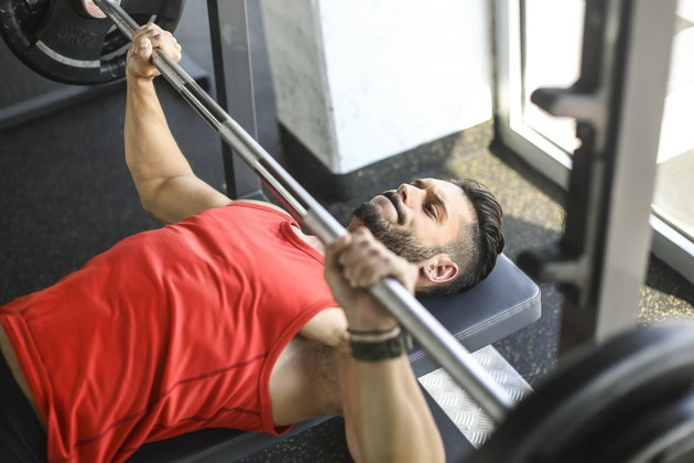 man in red tank top doing chest presses on a weight bench
