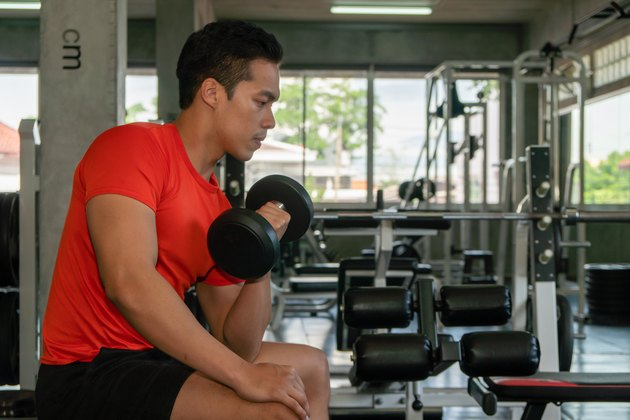 male having exercise lifting dumbbell in gym