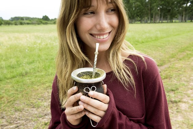Young woman drinking mate in gourd