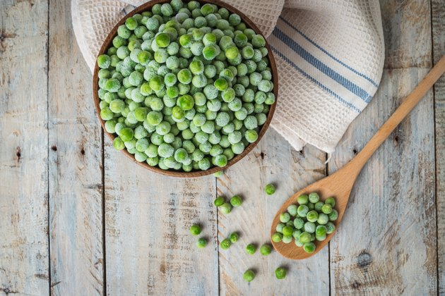 Frozen peas on a wooden table