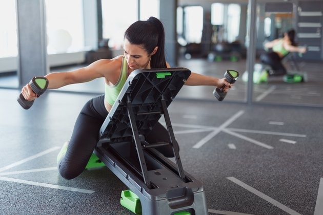 Woman training on step platform with dumbbells