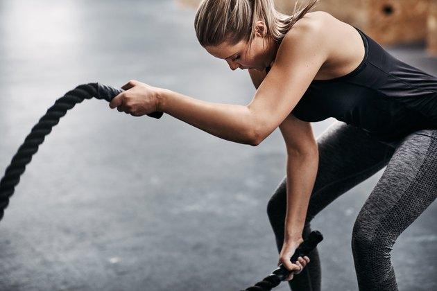 Fit jeune femme balançant des cordes pendant l'entraînement de gym