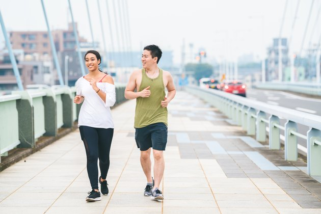 Multi-ethnic couple running together in city