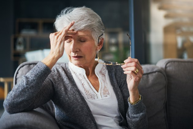 senior woman at home suffering from dizziness and blurred vision due to low blood pressure
