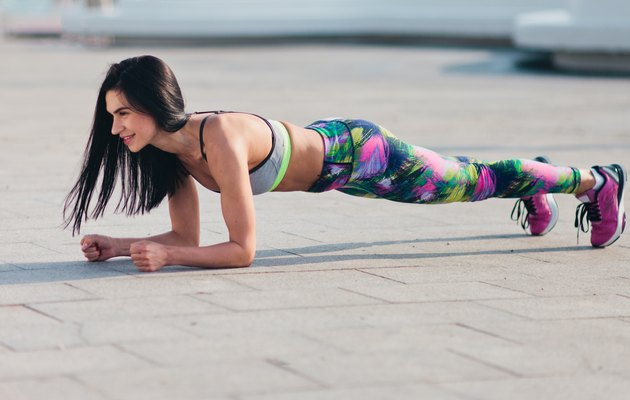 Young fit woman in sportswear doing plank exercise outdoors