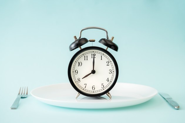 An alarm clock on a plate, intermittent fasting concept