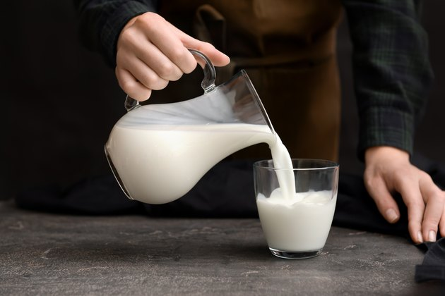 Woman pouring fresh milk from jug into glass on table