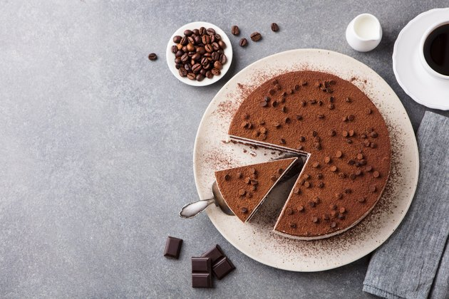 Tiramisu cake with chocolate decoration on a plate. Grey stone background. Top view. Copy space.