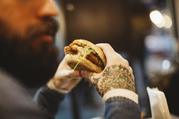A man with tattoos eating a sandwich at a restaurant