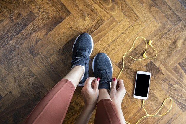 Woman tying shoelace before workout with smartphone and headphones