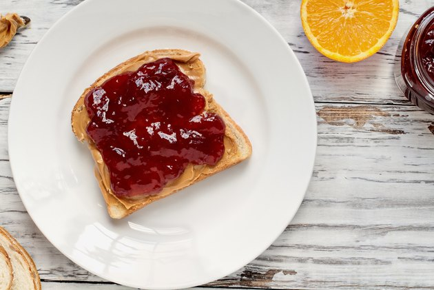 Open face homemade peanut butter and strawberry Jelly sandwich