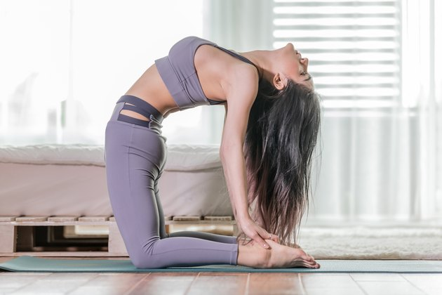 Attractive Asian woman practice yoga Ustrasana pose or yoga Camel pose to meditation in bedroom after wake up in the morning Feeling so comfortable and relax, Yoga for Health care Concept
