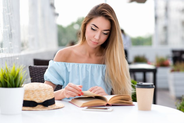 Young and beautiful girl with long hair. On the table is a cup of coffee and tea. Woman reading a paper book on the table. An interesting novel, turns the page. In the summer in the café sun terrace.