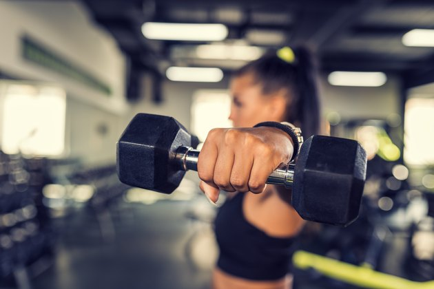 Woman in the gym doing a lateral dumbbell raise