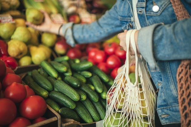 Vegetables and fruit in reusable bag on a farmers market, zero waste concept