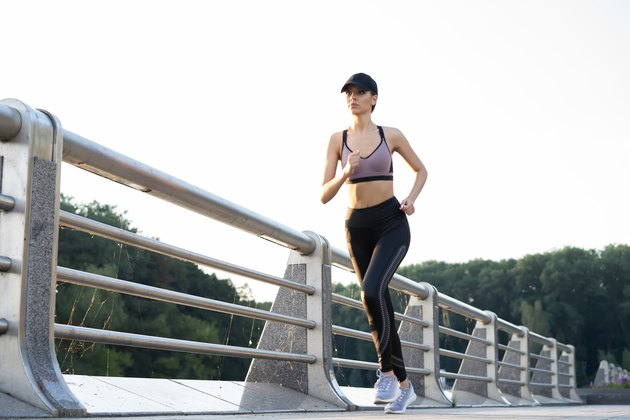 Young pretty woman with perfect slim body running outdoors. Fitness and running concept.