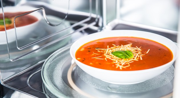 Inside view of new clean staniless microwave oven with a tomato soup in white plate