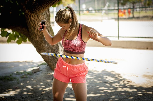 Young woman hula hooping outdoors