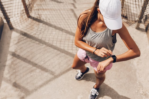 Female runner looking at smart watch heart rate monitor