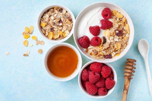 Greek yogurt in bowl with raspberries, honey and muesli on blue table top view.