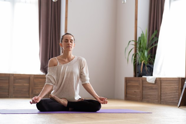 Charming young woman in meditation on the floor