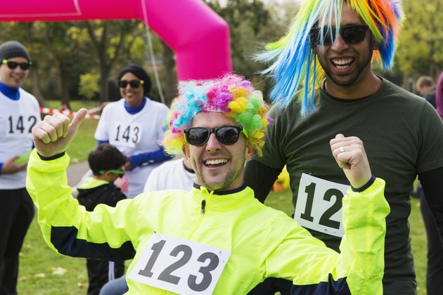Portrait enthusiastic male runners wearing wigs at charity run