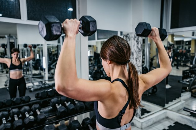Woman workout in gym with dumbbells