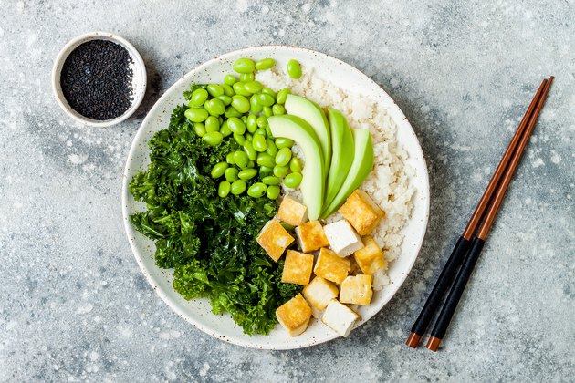 Cauliflower rice Buddha bowl with massaged kale, tofu, avocado and edamame beans. Vegan poke bowl