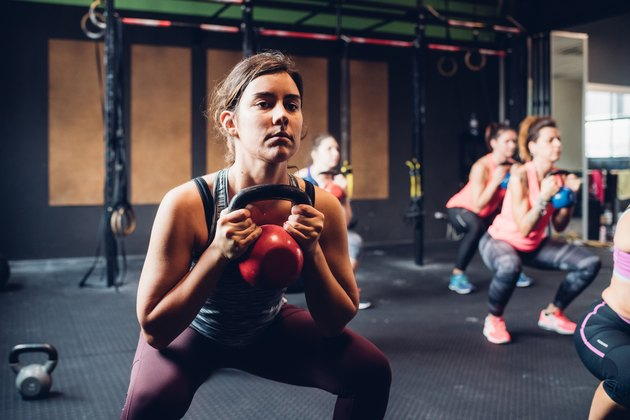 Women training in gym, squatting and lifting kettle bells