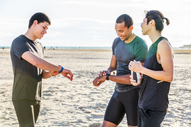 Male runners checking smart watch fitness trackers on sunny beach