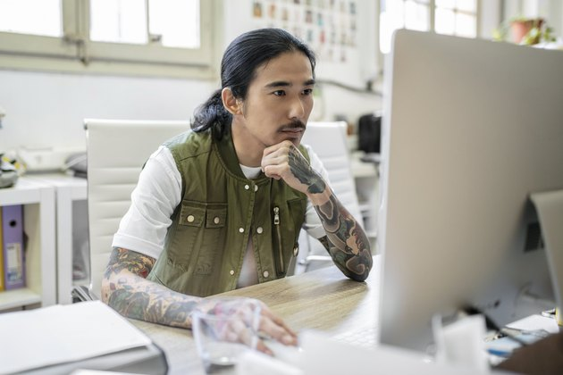 Businessman with tattoo using computer at desk