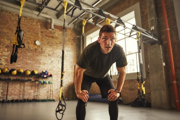 Young athletic man in sportswear looking exhausted during workout at gym with TRX