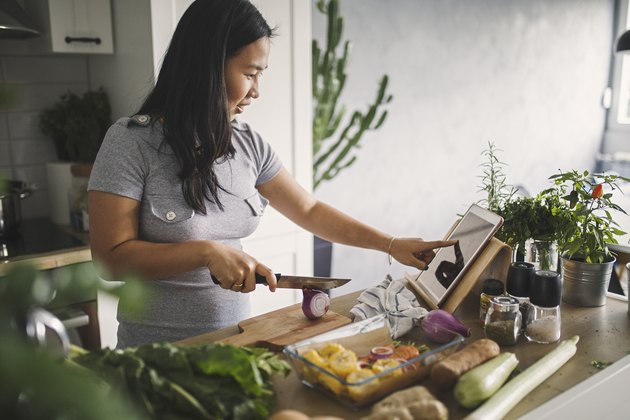 Asian woman using tablet in kitchen and cutting vegetables to meal prep a healthy meal