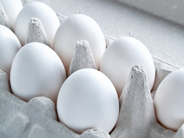 White fresh raw chicken eggs lie in a container for carrying eggs