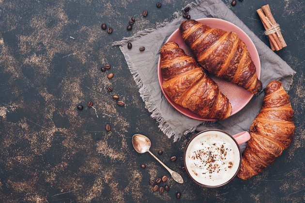 Croissants with coffee on a dark surface, top view, copy space.